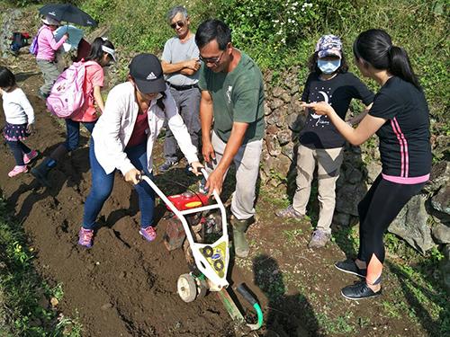 都市農夫在田裡學伙伴指導下操作中耕機。