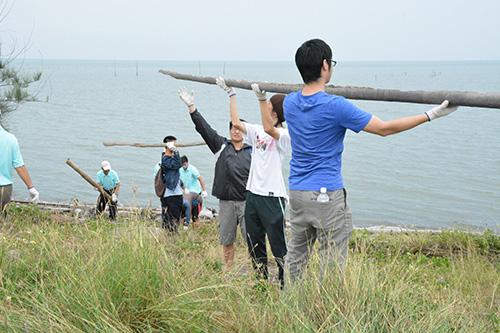 南華大學發起淨灘,以人龍方式共同傳送鰲鼓濕地西堤外側漂流竹木。