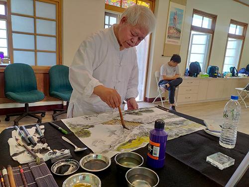 南華大學USR計畫與在地文史工作者交流,學子踏查大林百年古戰場 認識地方史蹟。林晉老師揮毫重現歷史的地景
