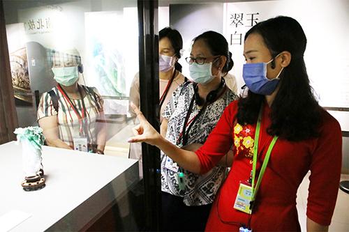 越南新住民范氏月(右1)指出翠玉白菜只有18公分高,但卻雕工精細,令人陶醉